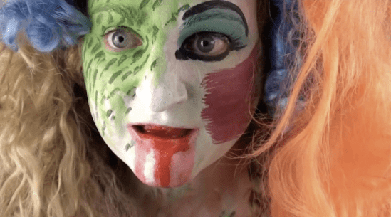 Bailey Scieszka Fighting History with Lightning Video Duration: 7 mins 32 sec Courtesy of the artist. (Image depicting a still of a video. A close up of a face that is painted haphazardly like a clown with white, green, red, and blue, surrounded by wild orange hair.)