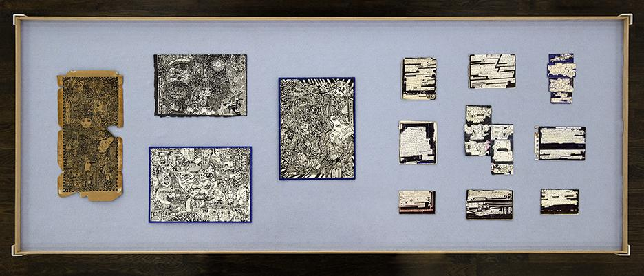 HEALING ARTS!, installation view, 2019 (Aerial view of works by Jose Lopez and Melvin Way installed in a vitrine. Lopez's four intricate drawings are arranged on the left half of the table. The work to the far left is on rough piece of brown paper. The other three are black line drawings on white paper with a black border. On the left side are Way's nine small drawings arranged in a three by three grid. The dense drawings are filled with micro texts and symbols, surrounded by bold areas of black or blue ink.)