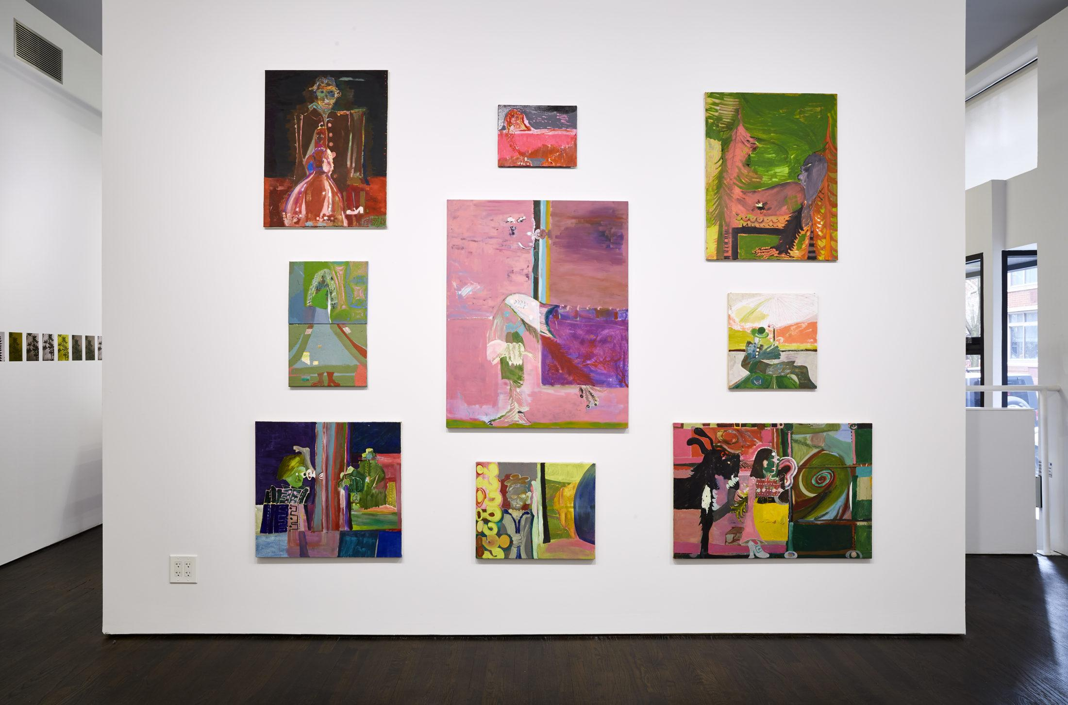Nine paintings installed salon style on a white wall.