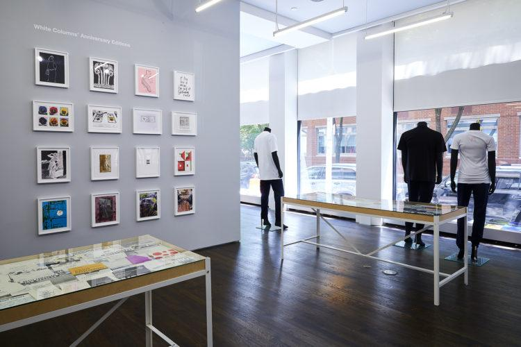 Gallery view of a wall displaying sixteen White Columns Anniversary Editions. Two vitrines are placed in front of the wall, and to the right stand three mannequins, facing the window.