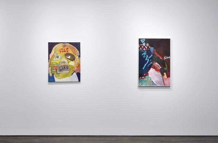 Frontal view of two paintings that are similar in size. The painting to the left portrays a figure with a distorted green mask looking up. To the right is an abstract painting of an array of shapes in hues of red and blue.